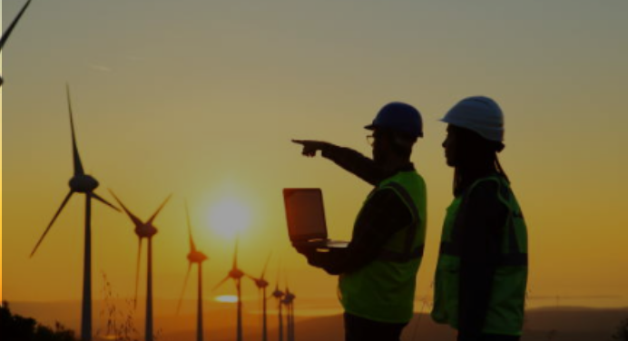 Two workers standing next to each other, one is holding a computer and pointing to wind turbines illustrating the word energy.