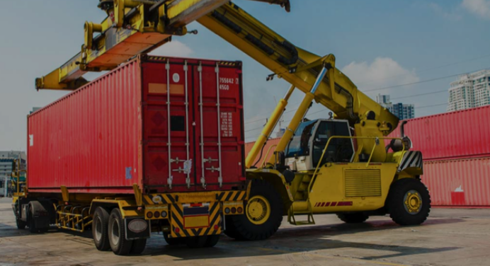 A construction vehicle loading a freight container on to an 18 wheel truck illustrating the words intermodal freight.
